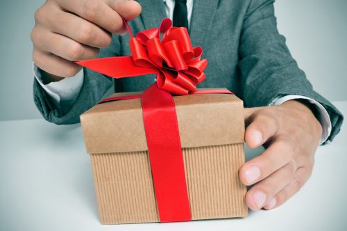 man wearing a suit sitting in a table opening a gift with a red ribbon